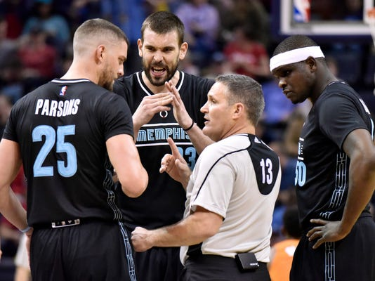 FILE - In this Feb. 28, 2017, file photo, Memphis Grizzlies forward Chandler Parsons (25), center Marc Gasol (33) and forward Zach Randolph (50) talk with referee Monty McCutchen during the first half of the team's NBA basketball game against the Phoenix Suns in Memphis, Tenn. McCutchen left his job on the floor during this season to become the league's vice president and head of referee development and training. With tensions high this season with both players and coaches, he's been conducting respect-for-the-game sessions with each team in hopes of creating a stronger working relationship. (AP Photo/Brandon Dill, File)
