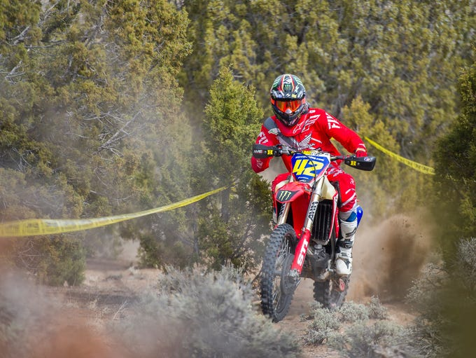 A rider blasts his way though vegetation during the