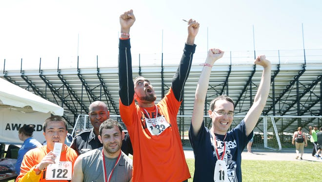 Center, Jacomo Peden-Falcone of Rochester celebrates his 100m dash win during the state Special Olympics at the College at Brockport.