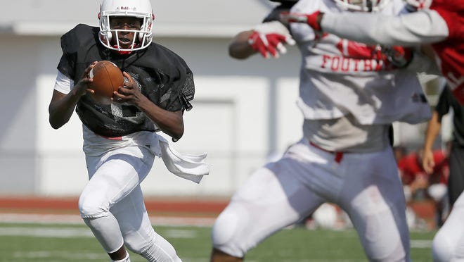 Deshaunte Jones, senior quarterback, breaks to the outside and looks for running room during practice, Saturday, Aug. 8, at Colerain High School.