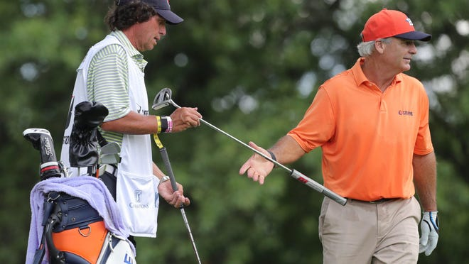Caddie Andy Davidson, a Firestone High School and University of Akron graduate, hands a putter to Blaine McCallister on the No. 13 green during the opening round of the Bridgestone Senior Players Championship on Thursday at Firestone Country Club.