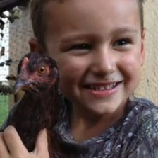 A photo taken from video shows a boy with his pet chicken.