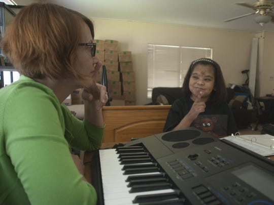 Carrie Rupnow-Kidd, Samaritan music therapist, works with Aracelis Mercado (Celi) during a therapy session at her family's Cherry Hill home.