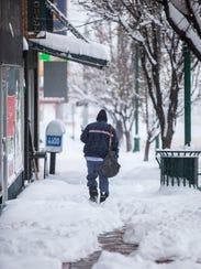 Cedar City mailman Henry Painter walks through snow