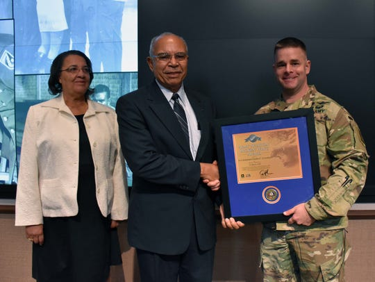 Army Brig. Gen. David Francis (right) presents West Melbourne resident Charles Coverley the Broken Wing Award as Coverly's wife, Genevieve, looks on last month at Fort Rucker in Alabama.