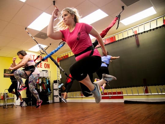 Emily Underwood does a running jump attached to a bungee cord during a workout class at P2 Personal Training on Wednesday, July 5, 2017, in Cape Coral. The bungees take pressure off joints and allow for a fun workout.