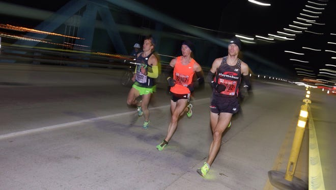 The first three runners cross the Ambassador Bridge into Canada during the 38th Annual Detroit Free Press/Talmer Bank Marathon in Detroit on Sunday, Oct. 18, 2015.