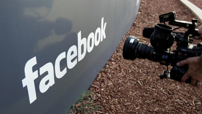 "In this May 18, 2012, file photo a television photographer shoots the sign outside of Facebook headquarters in Menlo Park, Calif. Facebook says it has removed 783 Iran-linked pages, accounts and groups from its service for what it calls ""coordinated inauthentic behavior,"" that is, misrepresenting who is running the accounts with the intent of disrupting politics and elections."