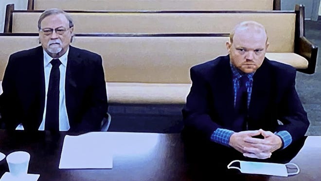 In this image made from video, Father and son, Gregory and Travis McMichael, from left, accused in the shooting death of Ahmaud Arbery in Georgia on Feb. 23, 2020, listen via closed circuit tv in the Glynn County jail in Brunswick, Ga., as Attornies argue for bond to be set at the Glynn County courthouse.