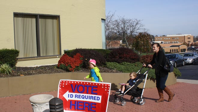 Dane Cesler, 3, left, leads her mother Paris Cesler, strolling in with her son Currie, 1, to vote mid-morning at the Gardens of Park Hills.