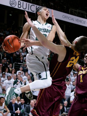 Michigan State's Travis Trice, left, drives and drawls a foul by Minnesota's Joey King during overtime on Feb. 26, 2015, at Breslin Center in East Lansing. Minnesota won 96-90.