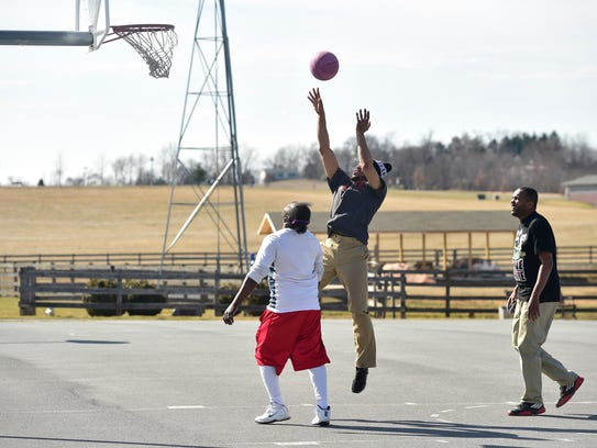Tito Toles, center, shoots the ball while playing a