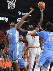Clemson forward Elijah Thomas (14) is guarded by North Carolina forward Sterling Manley (21), left, and guard Cameron Johnson (13) during the 2nd half on Tuesday, January 30,  2018, at Clemson's Littlejohn Coliseum.