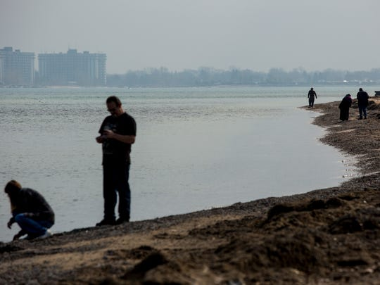 People walk along the shore of Lake Huron Wednesday,