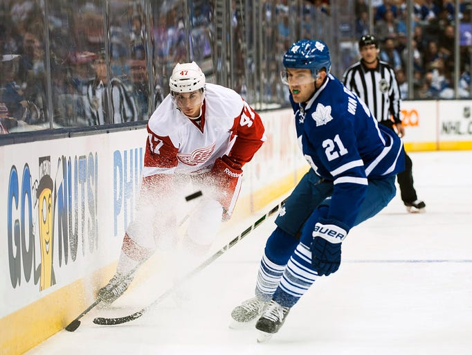 The Red Wings' Alexey Marchenko, left, takes the puck past the Maple Leafs' James van Riemsdyk during the first period of an exhibition game Friday, Oct. 3, 2014 in Toronto.