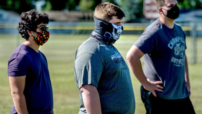 Illinois Valley Central football players keep their face masks on as they listen to instructions before the start of summer conditioning last month in Chillicothe.