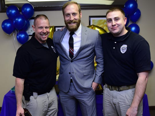 Adam Schlager, center, district manager GEO Reentry Service Center, is flanked by Franklin County Adult Probation officers Brent Smiley, left, and Geoff Harris during the 10th anniversary recognition event at the Loudon Street office on April 19, 2016.