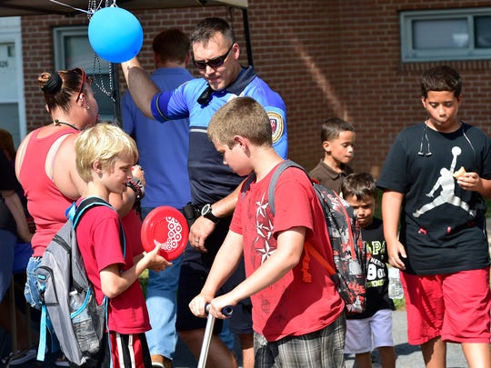 Kids interact with Matt Lynch of the Chambersburg Police. Chambersburg's National Night Out event was held Tuesday, August 2, 2016 at Franklin County's Housing Authority's Meadow Creek Development. The event featured music, face painting, food and bounce houses. During the annual event, first responders got a chance to interact with members of the community.