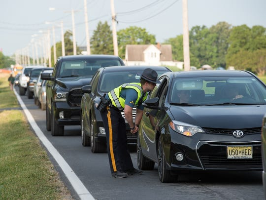 Delaware State Trooper First Class Benjamin Nefosky stops cars along Persimmon Tree Lane at the Firefly Music Festival in Dover.
