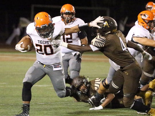 El Paso High running back Alex Velasco, 20, stiff arms Austin's Terrance Doyle 4, Friday night at Austin.
