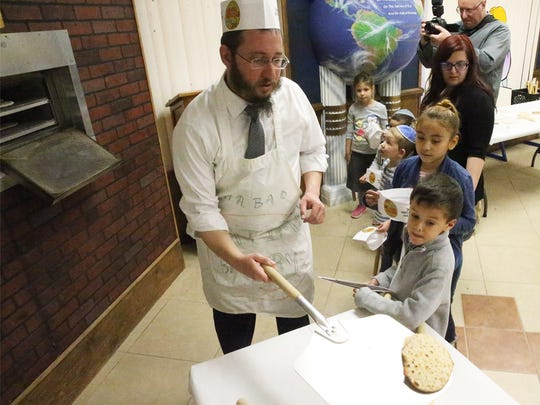 Rabbi Levi Greenberg, associate Rabbi at Chabad Lubavitch, 6615 Westwind Drive, takes a freshly baked Matzah out of the oven for children enrolled in the Chabad Education Center's spring camp.