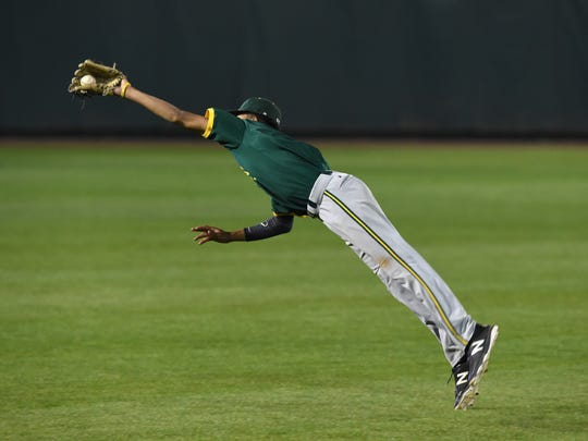 Manogues' Josh Rolling makes a diving catch during