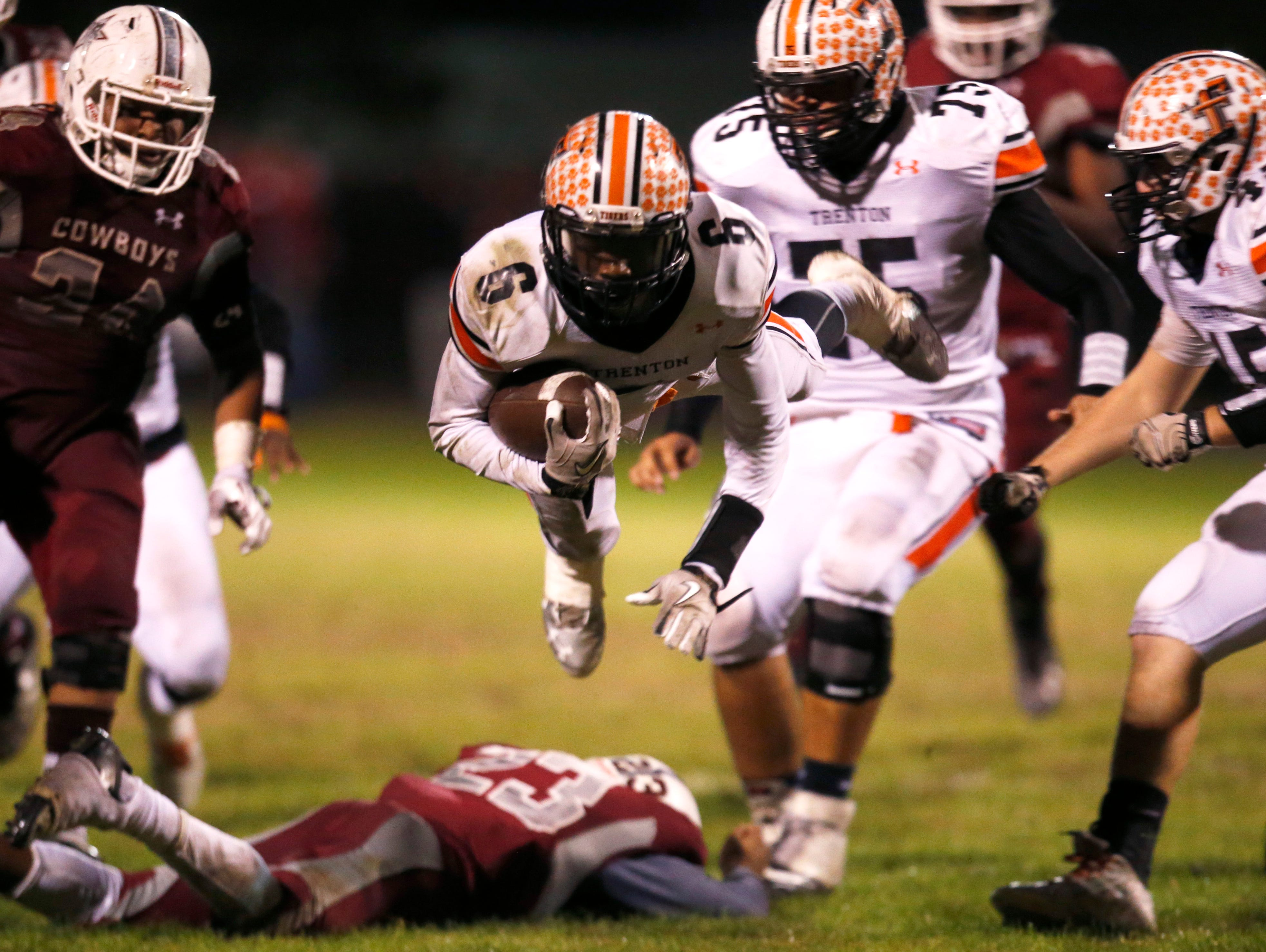 Trenton's Montrez Jackson dives forwards after being tackled by Madison County's Tinarus Irvine during their playoff game on Friday.