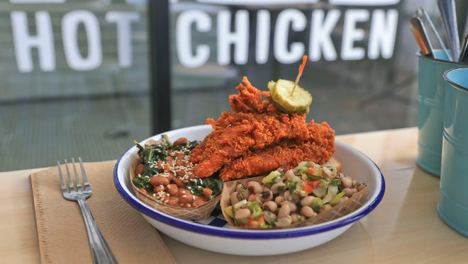 Royals hot chicken tenders with pinto beans and kale benne and black-eyed pea salad..