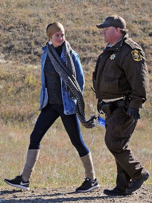 Shailene Woodley, left, is led to a transport vehicle by a Morton County Sheriff's deputy after being arrested at a protest against the Dakota Access pipeline near St. Anthony, N.D., on Oct. 10. 2016.