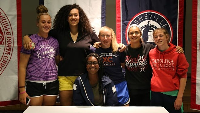 Carolina Day senior Mikayla Ray, seated, signed to play college basketball for Raleigh's William Peace earlier this week.