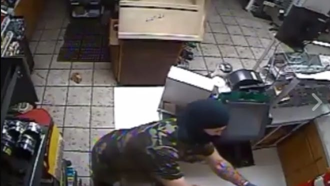 Glassboro police are searching for the identities of two suspects in connection with an Aug. 18 burglary of a Gulf gas station. One of the suspects, shown here in a  shot from the video, has a distinct tattoo on his left forearm.