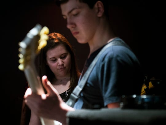Lauren Morrison, 15, left, plays bass on stage with
