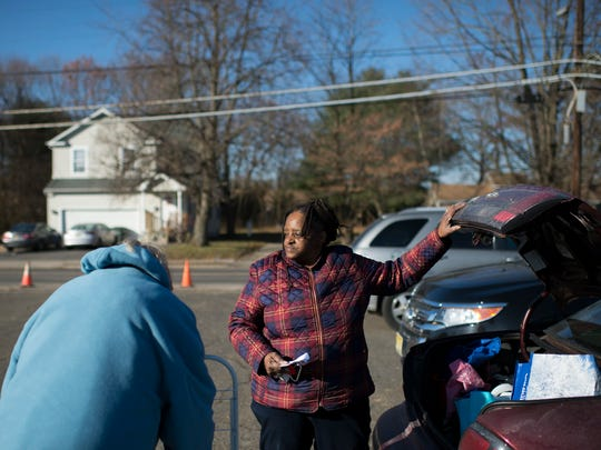 Renee Finney, right, of Glassboro finishes packing her trunk with groceries from the Food Bank of South Jersey Thursday, Dec. 21, 2017 in Glassboro, New Jersey. Parts of Glassboro is considered a 'food desert' by the USDA.