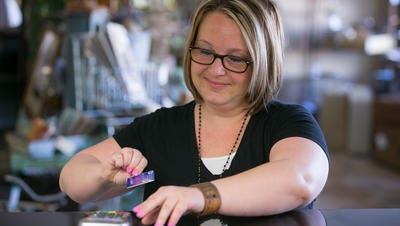 Co-owner Jenna Hollis demonstrates using her EMV chip credit card terminal at her store Rusty Saturday Home Decor in Phoenix on Monday, April 13, 2015. The U.S. credit card industry is switching to chip cards because it's harder for thieves to counterfeit them than it is to make fake magnetic-stripe cards. Most small business owners haven't made the switch to readers that can process chip-card transactions.