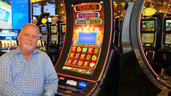 Lester Bullock, CEO of Victory Casino Cruises, sits next to one of the ship's state-of-the-art, curved LED slot machines.