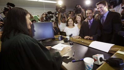 Todd Delmay, right, and his spouse, Jeff Delmay, second from right, Catherina Pareto, center, and her spouse Karla Arguello, left of center, smile after the couples were married by Miami-Dade Circuit Judge Sarah Zabel on Jan. 5, 2015.