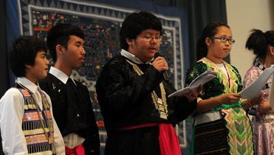 Bruce Thao, middle, reads from his script during a skit presented by John Muir Middle School students during the 2011 Hmong Heritage Month banquet at The Rose Garden in Wausau.
