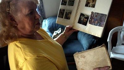 "In a 2005 file photo, Marie Faussett holds a picture album of her missing son, Tommy, and his Bible. Freddie ""Tommy"" Faussett Jr. went missing in March 1980 and was last seen at the Memorial Drive Post Office, where he worked. Recent DNA tests confirmed skeletal remains found in southern Indiana in 1999 are those of the Muncie man."