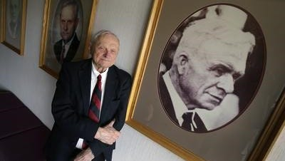 Oscar C. Boldt, Chairman of The Boldt Company, in front of pictures of his ancestors.