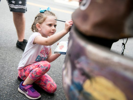 Liken Roche, 4, paints on the dragonfly bus while parked
