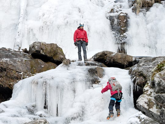 Anthony D'Ercole, a Fox Mountain Guides instructor, waits as Ethan Hale makes his way up the frozen Catawba Falls as they ice climb in Old Fort on Friday, Jan. 5, 2018. D'Ercole says with a properly trained guide ice climbing can be safer than the drive to the ice.