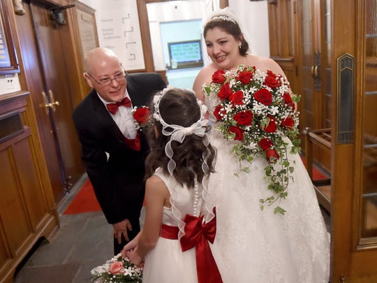 Adam Trout and his wife, Penny, tell his daughter Dessa, 10, what a wonderful job she did after their wedding at St. Paul's United Methodist Church on Saturday.