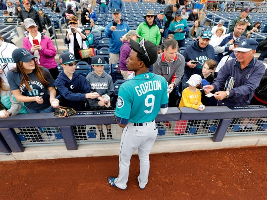 Seattle Mariners center fielder Dee Gordon gives autographs to fans before a baseball spring exhibition game against the San Diego Padres, Friday, Feb. 23, 2018, in Peoria, Ariz. (AP Photo/Charlie Neibergall)