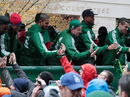 Portland Timbers players celebrate with fans during the MLS champions parade through Portland, Ore., Tuesday, Dec. 8, 2015.  The Timbers defeated the Columbus Crew 2-1 Sunday in the MLS Cup soccer final.