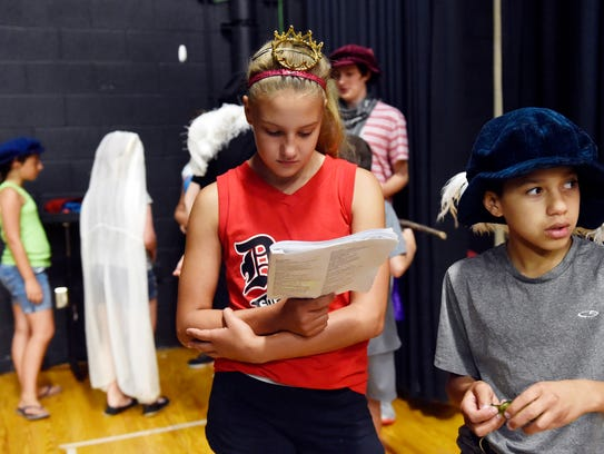 Kylie Snelbaker, 11, reviews the script during a rehearsal