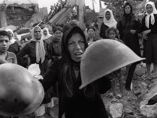 Bill Foley photograph of a Palestinian woman brandishes helmets during a memorial service in Beirut for victims of Lebanon's Sabra refugee camp massacre September 27 1982. She claimed the helmets were worn by those who massacred hundreds of her countrymen.