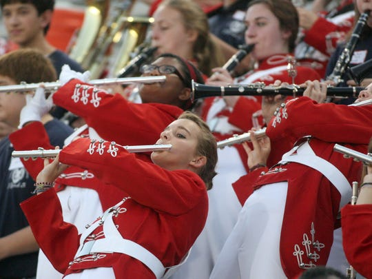 Wind instrument players in the Leon High School Marching Redcoats play during a football game.