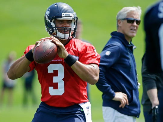 Seattle Seahawks quarterback Russell Wilson passes during NFL football practice as Seattle Seahawks head coach Pete Carroll looks on at right, Tuesday, June 6, 2017, in Renton, Wash. (AP Photo/Ted S. Warren)