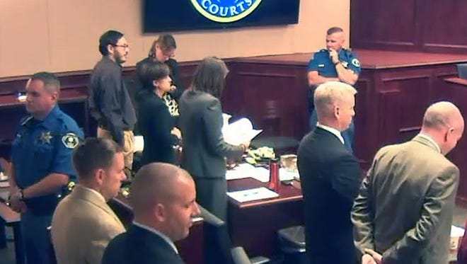 In this image made from Colorado Judicial Department video, James Holmes, fifth from left in dark shirt, stands in court on the first day of penalty phase 3 in his trial, in Centennial, Colo., on Tuesday, Aug. 4, 2015. The jury in the Colorado theater shooting trial will hear even more heart-wrenching testimony from those who lost loved ones in the attack, as prosecutors begin their final push to have Holmes sentenced to death. (Colorado Judicial Department via AP, Pool)