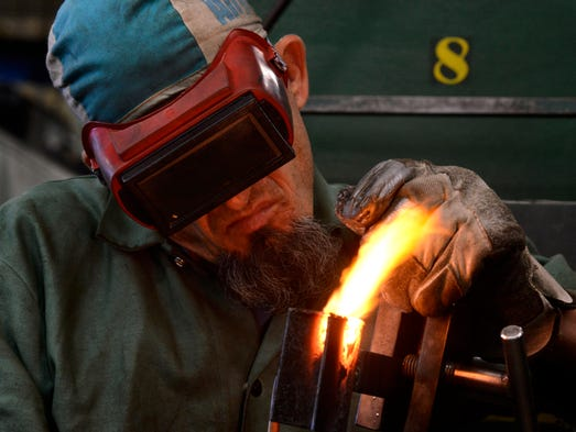 Gary McKissack welds in class as Gov. Rick Snyder and